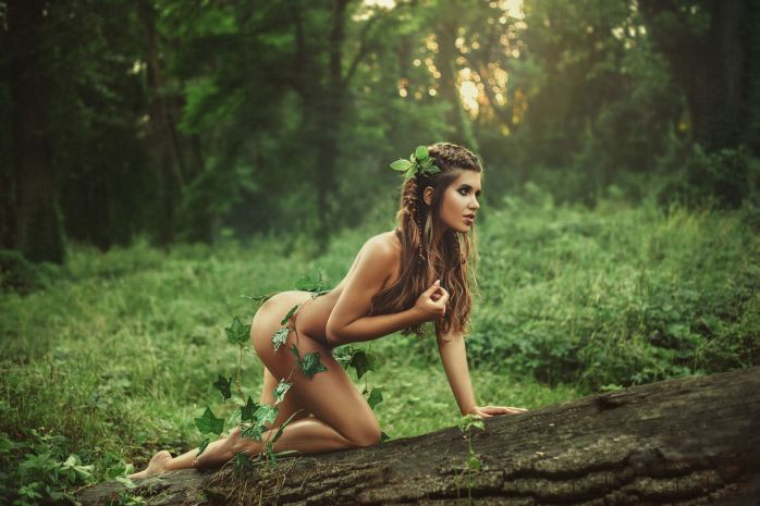 Sexy girl in clothes from leaves. Fantasy picture. Creative colors